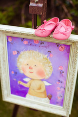 Little pink shoes stand on the painting of an angel