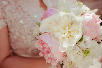 Bride in rich dress holds a bouquet of peonies