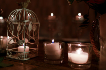 White candles put in low glasses and white bird cage