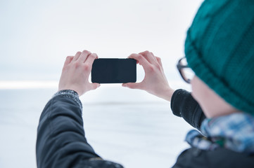 Woman taking picture on mobile phone in winter