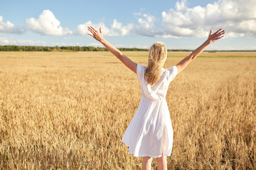 happy young woman in white dress on cereal field