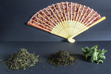 Chinese tea mix and hand fan on dark background