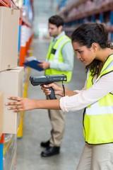 Female warehouse worker scanning box