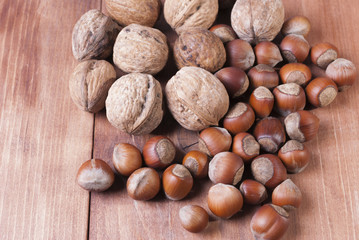 Mix of nuts on wooden background.