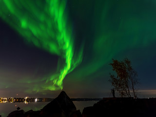 Northern lights over sea and a city in the background