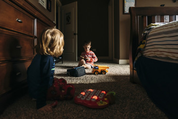 Boys playing with toys while sitting on floor at home