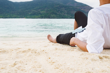 Businessman lying relaxing on sand beach look out to sea in holi