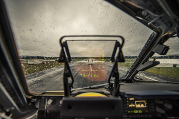 Airplane on runway against sky seen through wet windshield