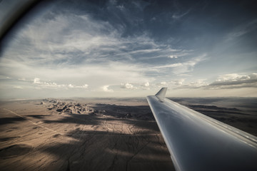 Cropped image of aircraft wing flying over landscape