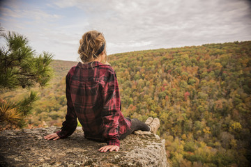 Rear view of woman looking at view while sitting on cliff against cloudy sky