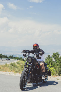 Portrait of biker with cruiser motorcycle on road against sky