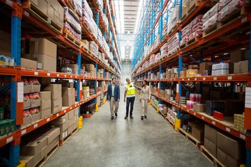 Warehouse team discussing while walking