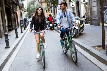 Happy young couple cycling in the city.