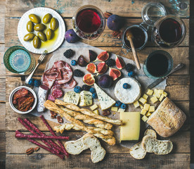 Wine and snack set with various wines in glasses, meat variety, bread, green olives, figs, nuts and berries on wax paper over rustic wooden background, top view, horizontal composition