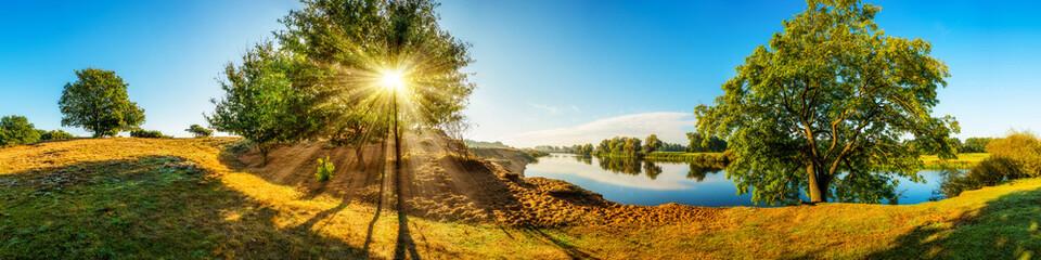 Landschaft im Herbst - Panorama mit Fluss und Bäumen bei Sonnenaufgang