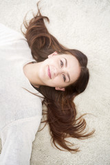 young woman lying on carpet and smiling at camera