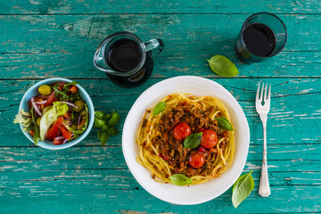 Delicious bavette pasta with bolognese sauce and fresh herbs on wooden table. Italian food.