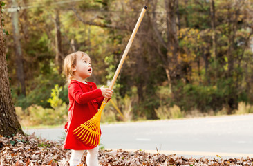 Toddler girl playing with a rake outside in autumn