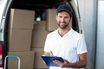 Portrait of delivery man holding a clipboard in front of van
