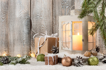 Christmas candle lantern, gift boxes and decoration on snow
