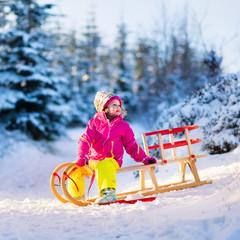 Little girl having fun on a sledge in snowy winter forest