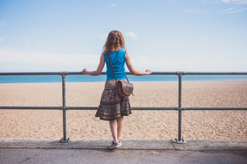 Young woman by railing on the beach