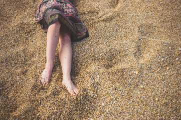 Legs of a young woman on pebble beach