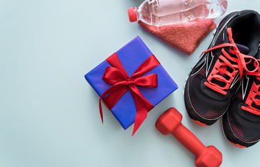 fitness equipment and gift on blue background