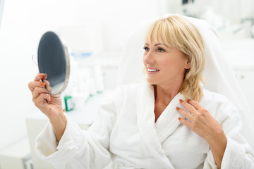 Happy mature lady is satisfied with skincare treatment