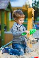 happy little boy playing in sandbox at playground