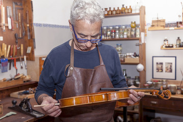 portrait of mature violin maker while testing the violins in his