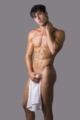 Naked muscular man covering crotch with shirt