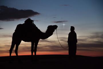 "Africa, North Africa, Tafilalet, Erfoud, Merzouga, Erg Chebbi, Dromedary (Camelus dromedarius) camel with Tuareg man, at sunset. ""Star of Bethlehem"" effect added digitally."