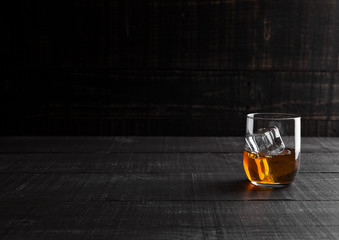 Glass of whiskey with ice on wooden background