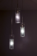 Chandelier made of glass and metal, it is hanging ceiling light. Lamp lights in the dark, room interior.