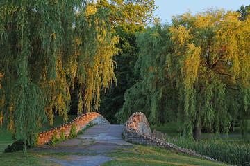 Onondaga Park Syracuse-Weeping willows framing a sun-kissed stone bridge in Syracuse NY