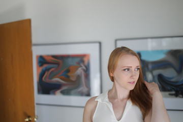 Red Haired Woman in WhiteTop at an Art Gallery