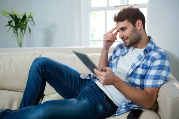 Man using digital tablet while relaxing on sofa