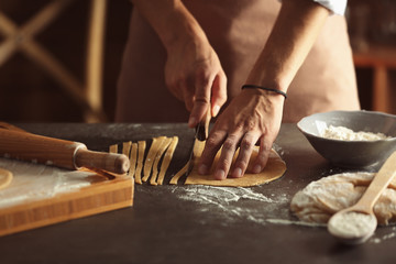 Male hands cutting pasta on kitchen table, close up view