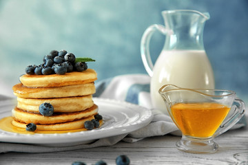 Plate of delicious pancakes with blueberries, honey and glass jug of milk on wooden table