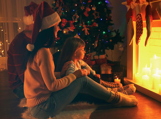 Family sitting near fireplace in living room decorated for Christmas