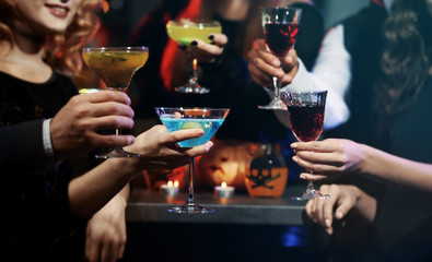 People drinking colorful cocktails at Halloween party, closeup