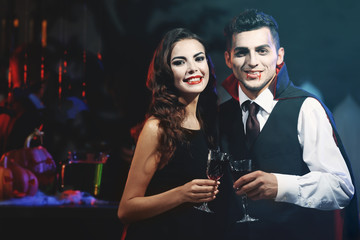 Young people dressed as vampires drinking cocktails at Halloween party