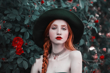 Red-haired girl with blue eyes and pale skin in a green hat and dress with a red belt. Woman with long red plait against the backdrop of bush peach roses.