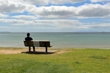 man sitting on bench looking out to the ocean