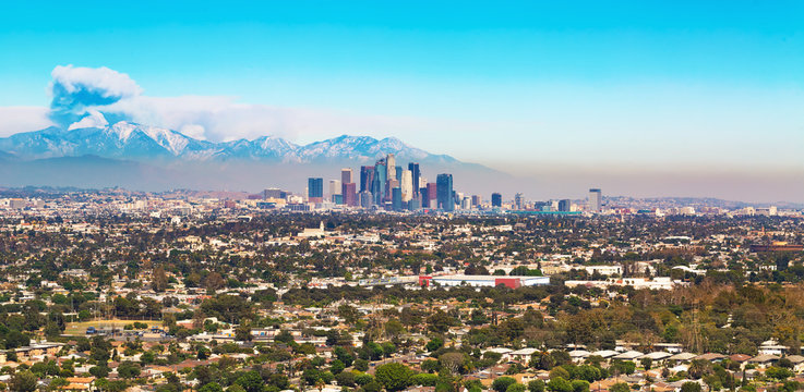 View of LA with smoke from a forest fire rising from the mountains