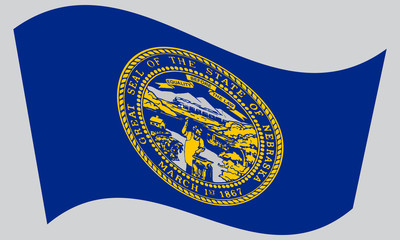 Flag of Nebraska waving on gray background