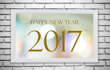 White wooden frame with Happy New Year 2017 on white brick wall