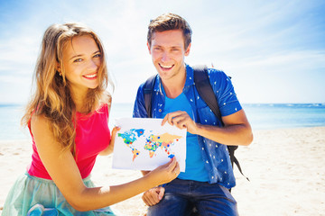 couple holding a map with travel destinations