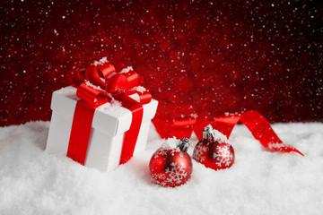 Christmas balls and gift box on snow.